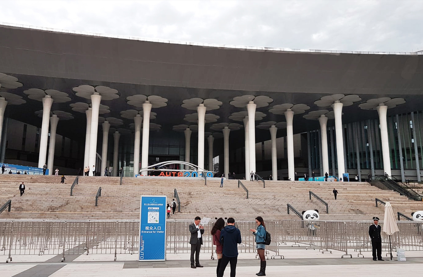 Exterior view of the Shanghai New International Expo Centre with extensive stairs and a tremendous entrance area with pillars which suggests the relevance of the third biggest industry show of the world. With the focus on digital vehicles and alternative driver systems, the fair offered a deep insight into the future of the driving experience.