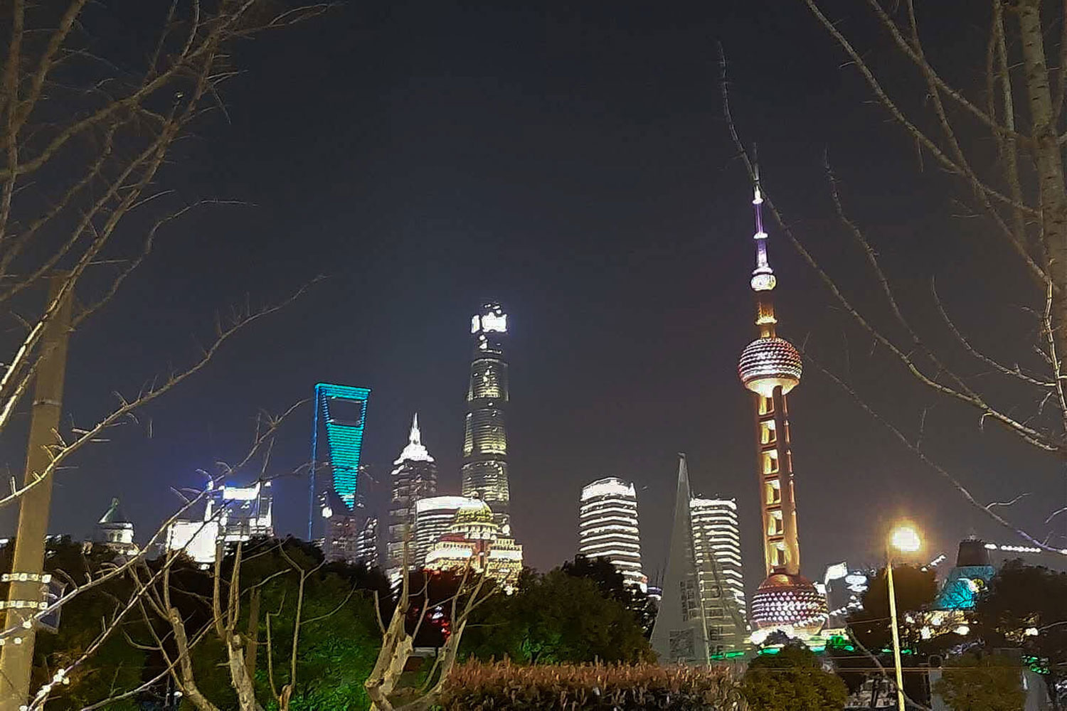 Distinctive illuminated skyscrapers of the global metropolis Shanghai at night. They shape the scape of the city and suggest an impression of modernity and innovation.