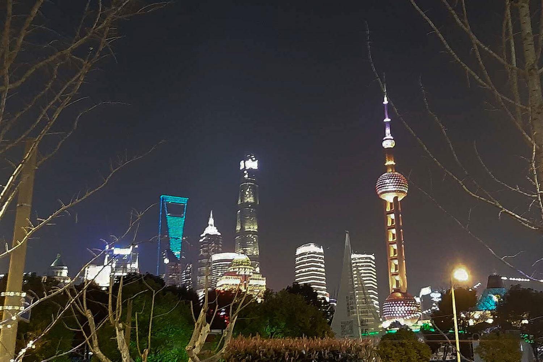 Markante beleuchtete Wolkenkratzer der Weltmetropole Shanghai bei Nacht, die das Stadtbild prägen und einen Eindruck der Modernität und Innovation vermitteln.