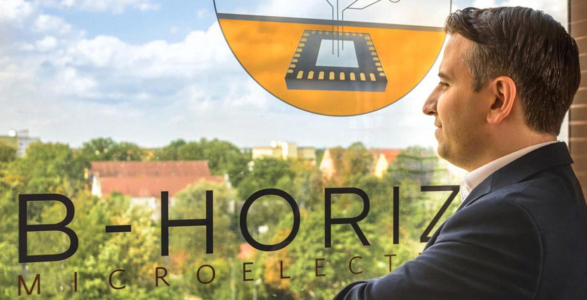 Gründer und Geschäftsführer Mohammad Kabany verkörpert mit seinem selbstbewussten Blick in die Zukunft am Fenster des Firmengebäudes mit dem B-Horizon Logo auf der Fensterscheibe die Vision des Unternehmens: weltweit erster und bester Partner im Bereich kundenorientierter Mikroelektronik-Entwicklung zu werden.