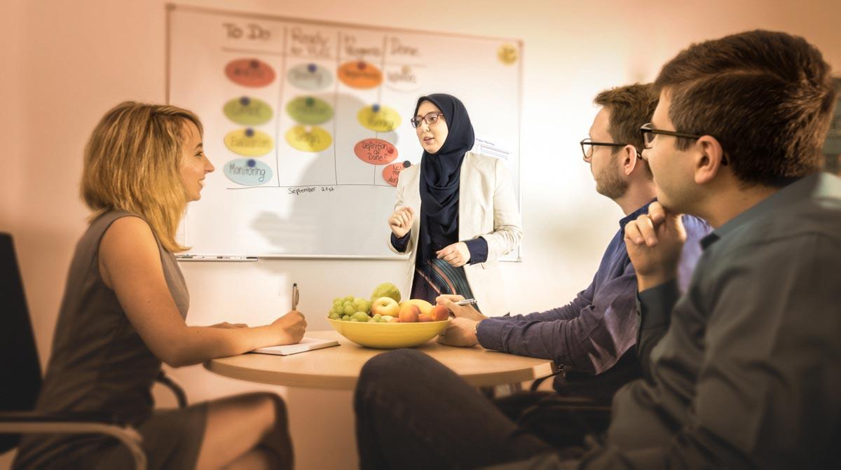 Zwei Kolleginnen und zwei Kollegen des B-Horizon Teams, die an einem Meeting beteiligt sind. Eine Kollegin mit Kopftuch erklärt gerade am Whiteboard den aktuellen Projektstand. Die anderen Mitarbeiter sitzen am Tisch davor, hören ihr konzentriert zu und notieren sich dabei das Wichtigste in ein Notizbuch. Das Bild verdeutlicht die Arbeitsatmosphäre bei B-Horizon, die auch von Diversität und Agilität geprägt ist. Wenn Sie Ihre Karriere bei B-Horizon starten, werden Sie Teil eines diversen, internationalen Teams, an einem der attraktivsten Standorte Deutschlands. Durch die verschiedenen Erfahrungen und Expertise der Mitarbeiter können komplexe Fragestellungen schneller und besser gelöst werden. Dabei wird in der Arbeitsmethodik eine Mischung aus soliden Prozessstrukturen und agilem Projektmanagement angewandt.