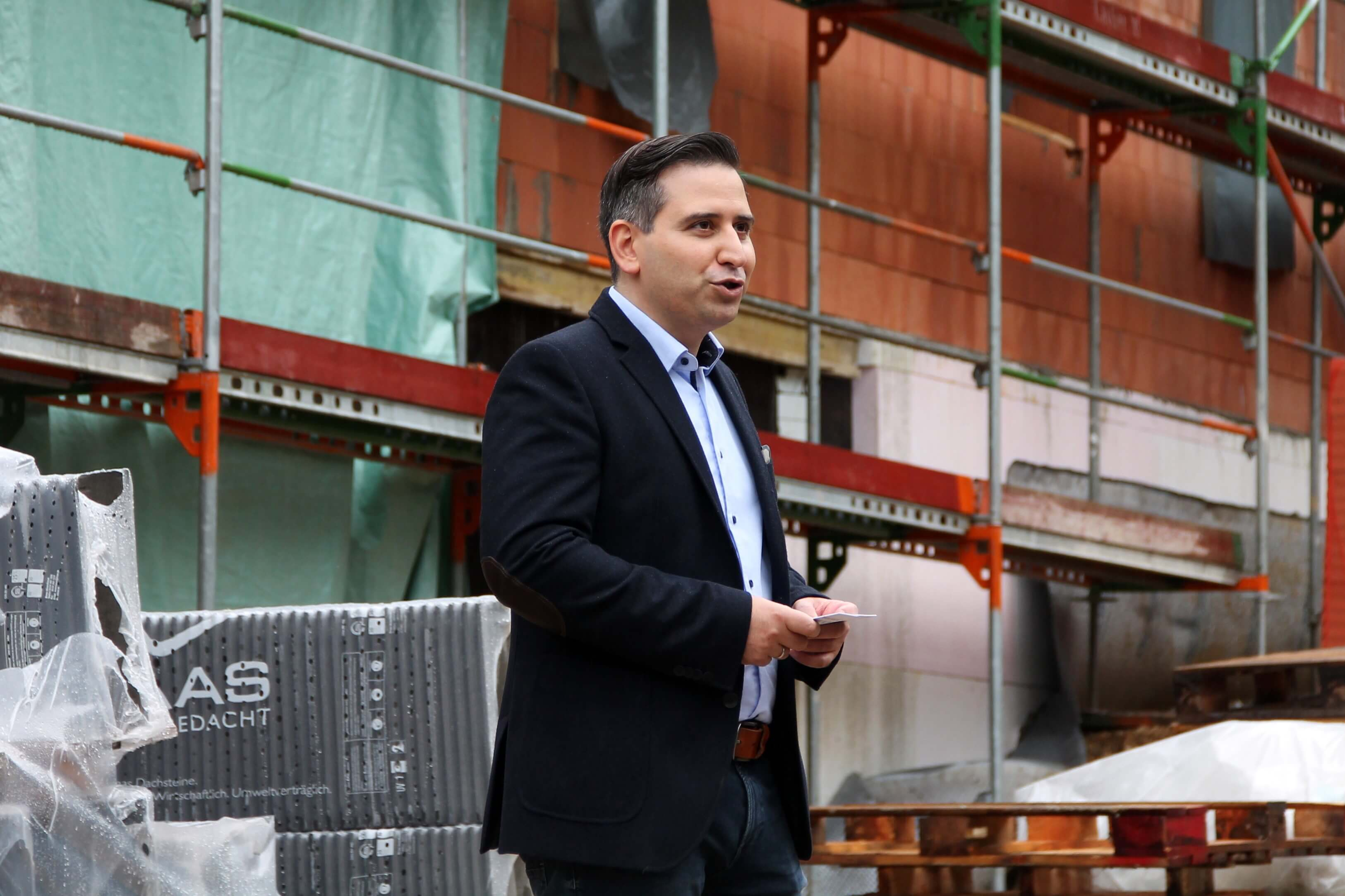 Founder and CEO Mohammad Kabany is giving a speech in front of the bare brickwork of B-Horizon's future headquarters at the topping-out ceremony in Sinzing. He also recalls the challenges which come with such an innovative and complex construction project.