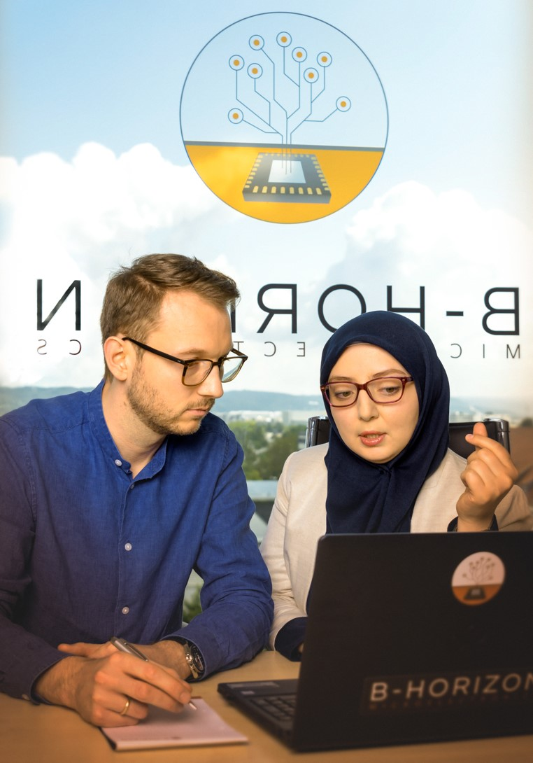 A male colleague with glasses and a female employee wearing a headscarf are sitting at the desk and discussing some results with a laptop computer. In the meantime, the male colleague is taking notes on a sheet of a pad. In the background the B-Horizon logo Is displayed at the window of the office building. Because B-Horizon aims to attract the best talents, the company offers an ample spectrum of benefits as an employer. Whoever starts his career at B-Horizon, gets attractive benefits in return, such as flexible working hours and new state-of-the-art workplaces.